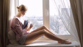Drömma kvinnan med ett boksammanträde på fönsterbrädan och se till och med fönstret stock video