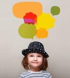 Drömma ungeflickan i hatt som ler och ser upp på många färgrika bubblor Arkivfoton