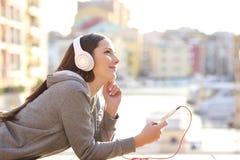 Drömmareflicka som lyssnar till musik på semester royaltyfria bilder