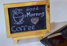 Drücken Sie den Kaffee des guten Morgens aus, der auf eine Tafel auf ihr und Smartphone, Laptop geschrieben wird stockbild