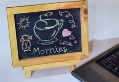 Drücken Sie den Kaffee des guten Morgens aus, der auf eine Tafel auf ihr und Smartphone, Laptop geschrieben wird stockbilder