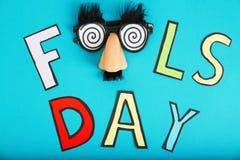 Drücken Sie ` Dummkopf ` s Tag-` und lustige Gläser auf Farbhintergrund aus Stockfotografie