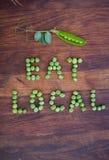 """Drücken Sie """"Eat Localâ€- aus, das von den grünen Erbsen und von der Erbsenhülse mit Blättern gemacht wird lizenzfreie stockbilder"""