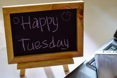 Drücken Sie glücklichen Dienstag aus, der auf eine Tafel auf ihr und Smartphone, Laptop geschrieben wird stockfoto