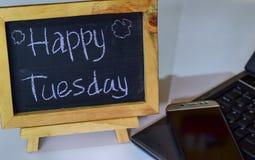 Drücken Sie glücklichen Dienstag aus, der auf eine Tafel auf ihr und Smartphone, Laptop geschrieben wird stockfotografie