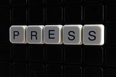 Drücken Sie Textwort-Titeltitel-Aufkleberabdeckungs-Hintergrundhintergrund Alphabetbuchstabebauklötze auf schwarzem reflektierend lizenzfreies stockfoto
