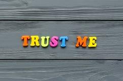Drücken Sie ` vertrauen mir ` von farbigen magnetischen Plastikbuchstaben auf grauem hölzernem Hintergrund aus lizenzfreie stockfotografie