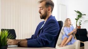 Dręczy ostrości kobiety sztuk wideo gry na konsoli podczas gdy jej mąż pracuje na komputerze zbiory
