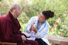 Dr eller sjuksköterska som ger läkarbehandlingen till den höga patienten Royaltyfri Fotografi