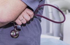 Dr. hands behind his back holding stethoscope.  Stock Photos