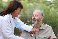 Dr with stethoscope checking senior patient. Stock Photos