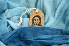 Dra en lycklig flicka på den pålagda blåa halsduken för etikettsetikett Arkivbild