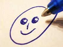 Dra en smiley med den blåa kulspetspennan, closeup arkivbild