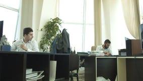 Dra i kontoret En ung man kastar ett stycke av papper på hans kollega och skrattar arkivfilmer