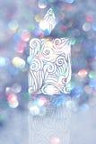 Dra stearinljuset med blåa bokehbakgrunder för juldag Royaltyfria Bilder