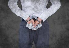 Dra tillbaka av affärskvinna i handbojor med pengar mot grå grungebakgrund Royaltyfria Bilder