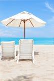 Dra tillbaka av de strandstolarna och paraplyerna på sand arkivbild