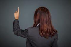 Dra tillbaka av den asiatiska affärskvinnan som trycker på skärmen med hennes finger Royaltyfri Bild