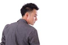 Dra tillbaka av den asiatiska mannen som bort ser till hans sida Fotografering för Bildbyråer