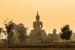 Dra tillbaka av den stora guld- buddha statyn på soluppgång med dimmabakgrund Royaltyfri Bild