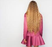 Dra tillbaka av den unga kvinnan med långt blont lockigt hår med sunt sken och att bära en purplklänning över en studiobakgrund Royaltyfri Bild