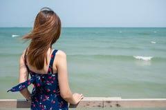 Dra tillbaka av en flicka som ser in i havet Royaltyfri Foto