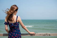 Dra tillbaka av en flicka som ser in i havet Arkivfoto