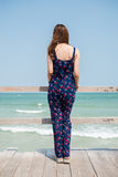 Dra tillbaka av en flicka som ser in i havet Arkivfoton