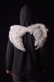 Dra tillbaka av en ung man med den svarta hoodien och vit befjädrade vingar Arkivbilder