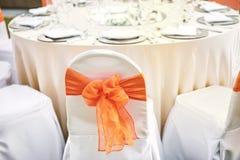 Dra tillbaka av för vita fönsterramen för organza räkningsstolar för spandex den orange för tabell för matställe för bröllopmotta Royaltyfria Foton