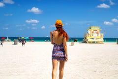 Dra tillbaka av flickan på Miami Beach Florida Atlantic Ocean, den unga kvinnan i kall utskrivaven mini- klänning går på den sand royaltyfria foton