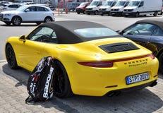 Dra tillbaka av gula Porsche 911 Carrera 4 GTS med tennispåsen Babolat Royaltyfri Foto