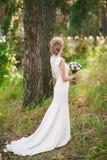 Dra tillbaka av härlig ung brud med bröllopbuketten i händer Royaltyfri Fotografi