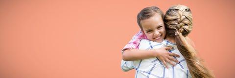 Dra tillbaka av hållande dotter för moder mot persikabakgrund Royaltyfri Bild
