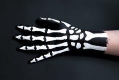 Dra tillbaka av handen som målas för att se som ben för halloween Royaltyfri Bild