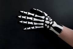 Dra tillbaka av handen som målas för att se som ben för halloween Arkivfoto