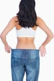 Dra tillbaka av kvinnan som rymmer hennes för stora jeans Fotografering för Bildbyråer