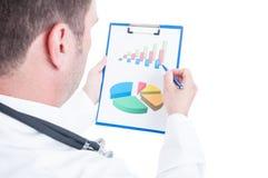 Dra tillbaka av läkaren som analyserar diagram eller statistik Arkivbild