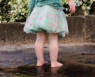 Dra tillbaka av lilla barnet som barfota står i pöl Royaltyfria Foton