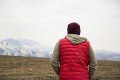 Dra tillbaka av man i röd waistcoat på bergbakgrunden fotografering för bildbyråer