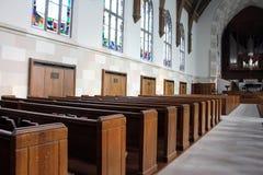 Dra tillbaka av rader av kyrkliga kyrkbänkar Royaltyfria Foton