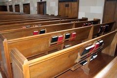 Dra tillbaka av rader av kyrkliga kyrkbänkar med biblar Royaltyfri Fotografi