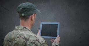 Dra tillbaka av soldat med minnestavlan mot grå bakgrund med grungesamkopieringen royaltyfri fotografi