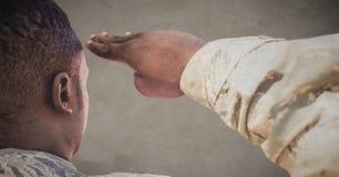 Dra tillbaka av soldaten som saluterar mot brun bakgrund med grungesamkopieringen royaltyfri fotografi