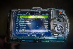 Dra tillbaka av vattentät punkt för den Olympus busen TG-2 och skjuta den Digital konsumentkameran Arkivfoton