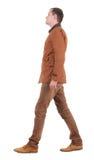 Dra tillbaka beskådar av gående stilig man i jeans och klår upp. Arkivbild