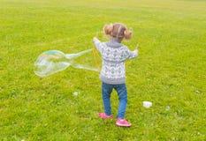 Dra tillbaka i Park behandla som ett barn flickan med sådana stora bubblor Royaltyfri Fotografi