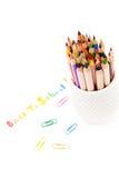 Dra tillbaka till blyertspennor för skolatext och färgpennaregnbågeöver vit backg Royaltyfri Bild