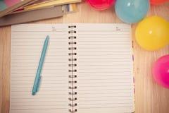 Dra tillbaka till skolabakgrund med anteckningsboken och den färgrika bollen, vinta Arkivfoton