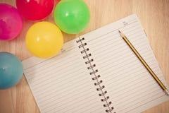 Dra tillbaka till skolabakgrund med anteckningsboken och den färgrika bollen, vinta Royaltyfri Fotografi